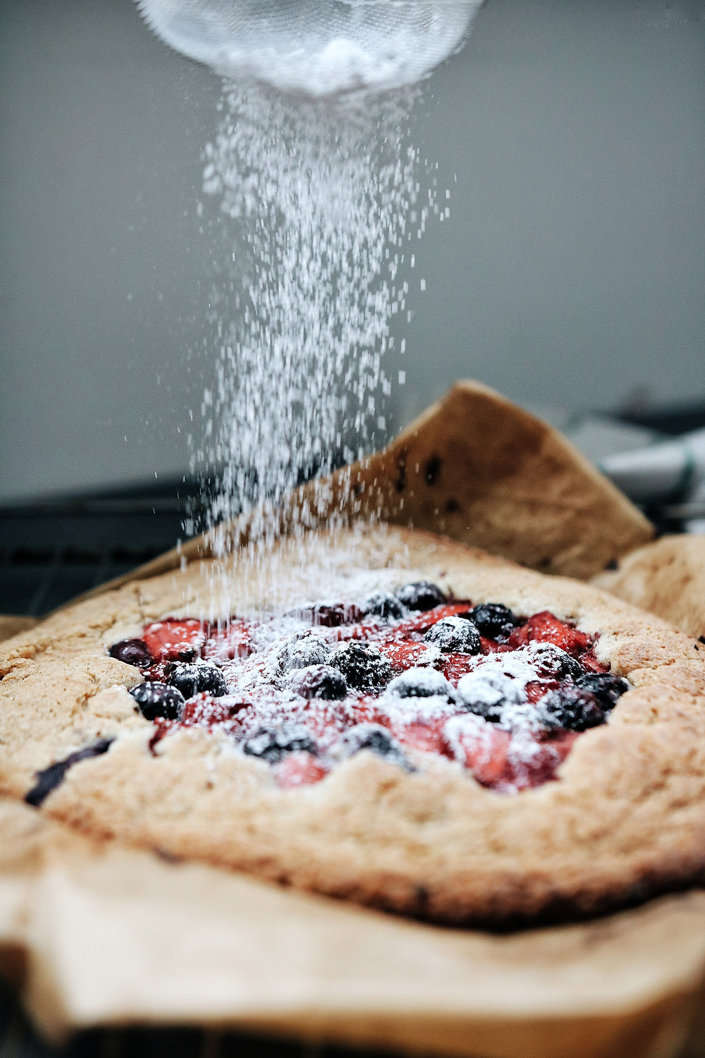 Dusting the strawberry buckwheat galette with sugar.