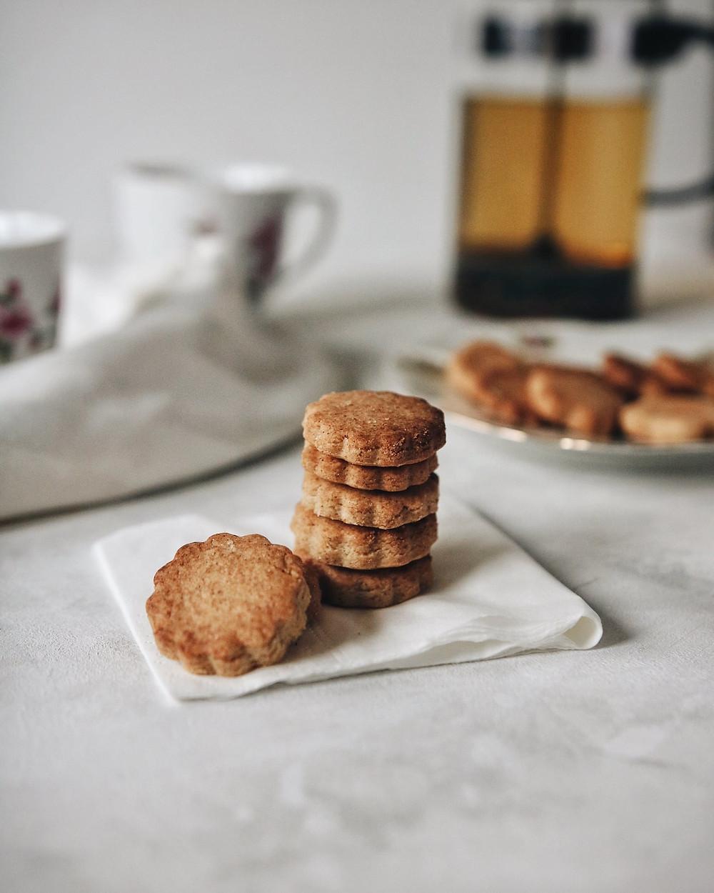 Bezglutenski keksići od kardamoma na bijeloj površini, s čajem i šalicama u pozadini.