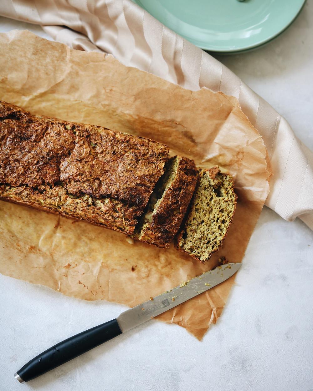 Pogled odozgo na kruh od tikvica sa začinima. Kruh razrezan na fete, na papiru za pečenje, na bijeloj podlozi.