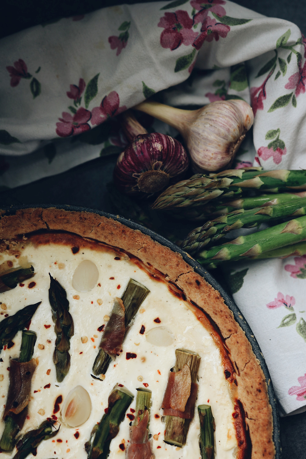 Gluten free asparagus tart, with goat cheese and prosciutto seen from above. In the upper right corner some garlic and asparagus stalks are seen, as well as a floral kitchen rag.