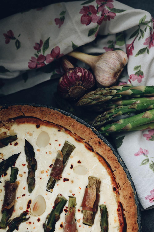 Slika tarta od kozjeg sira, sa šparogama motanima u pršut i češnjakom.