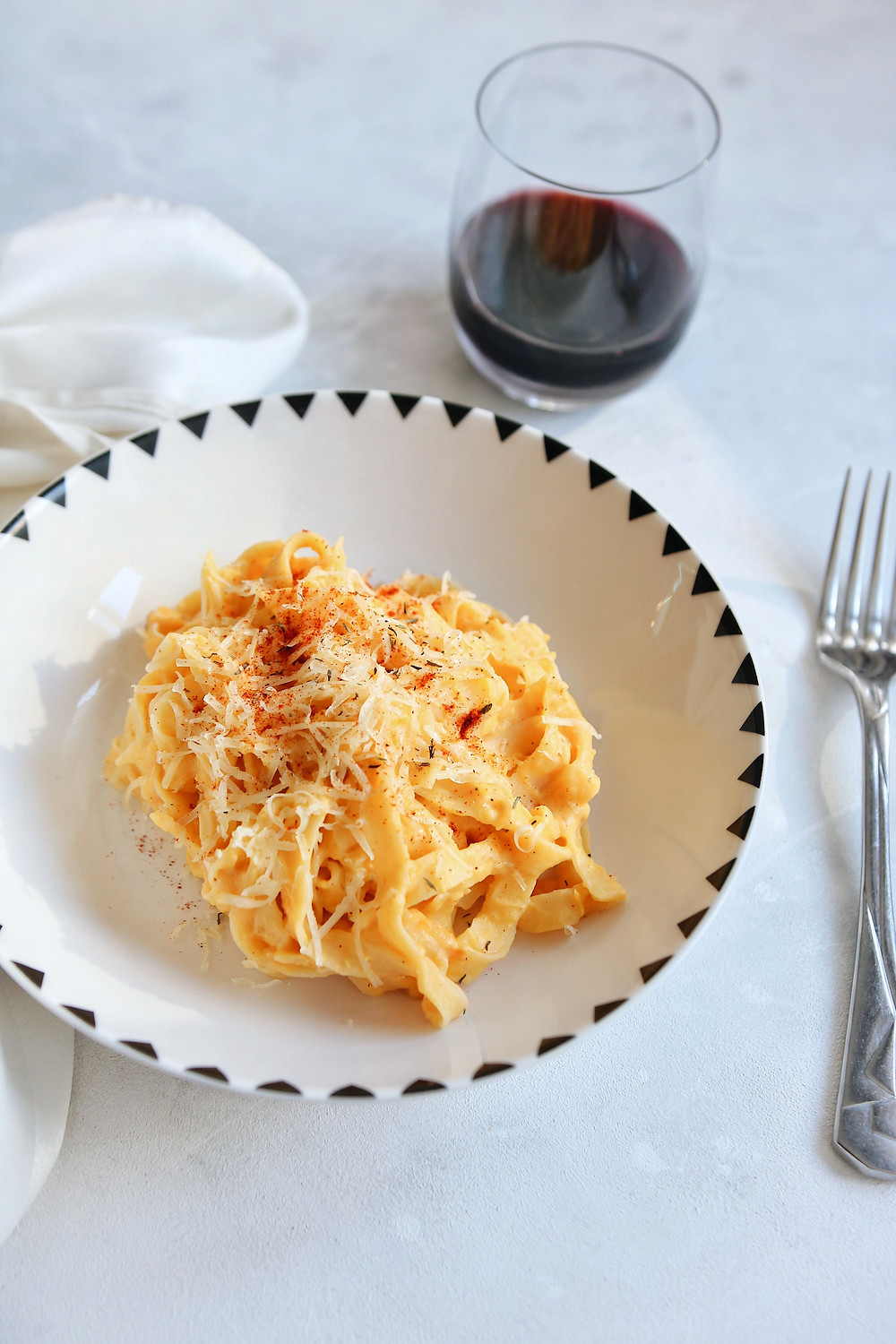A plate with pasta and butternut squash sauce on a white background, with napkin, red wine and fork in the image.
