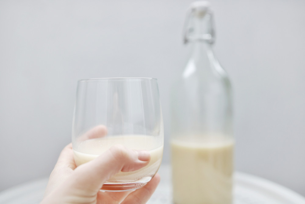 Hand holding a glass filled with flax milk, a glass bottle in the background