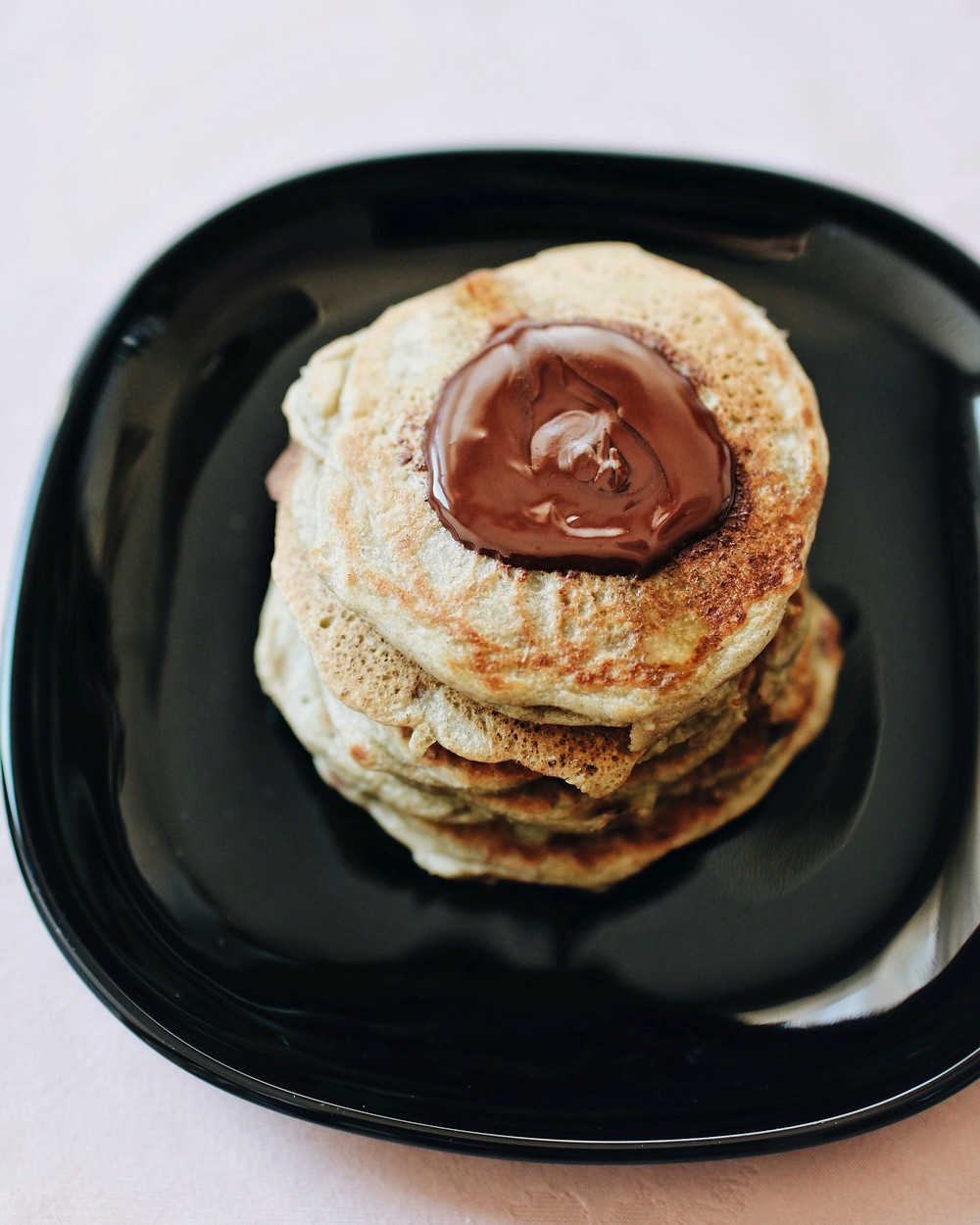 Birds eye view of gluten free and dairy free coconut matcha pancakes with dark chocolate melted on top.