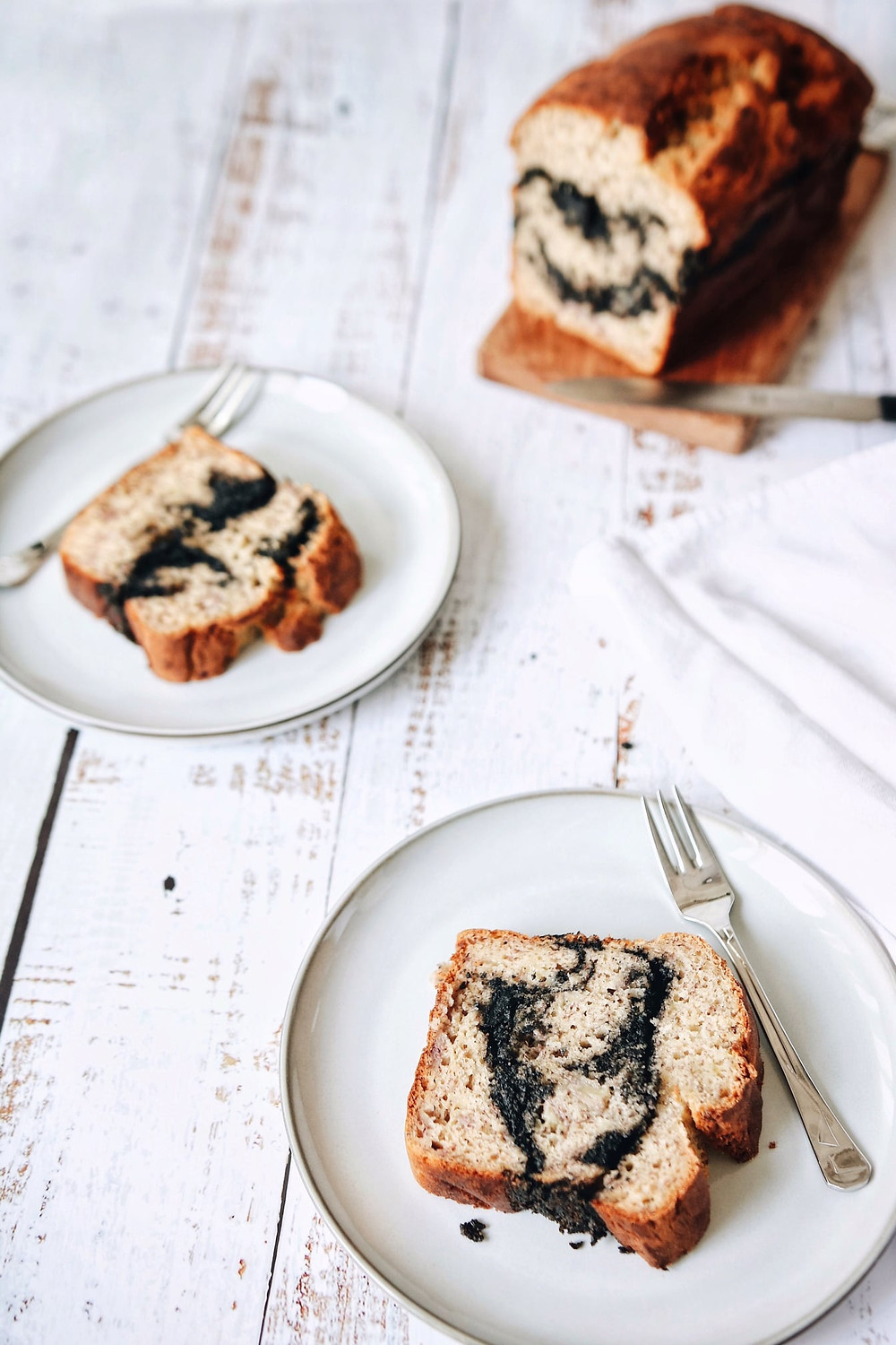 Two cut pieces of a gluten free banana bread with a black sesame paste swirl on plates on a white background, the rest of the loaf is on a cutting board in the background.