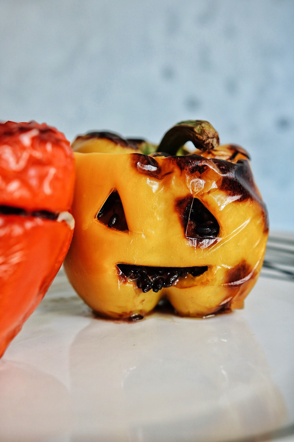 A yellow stuffed bell pepper carved like a jack o lantern with black rice coming out of its carved mouth.