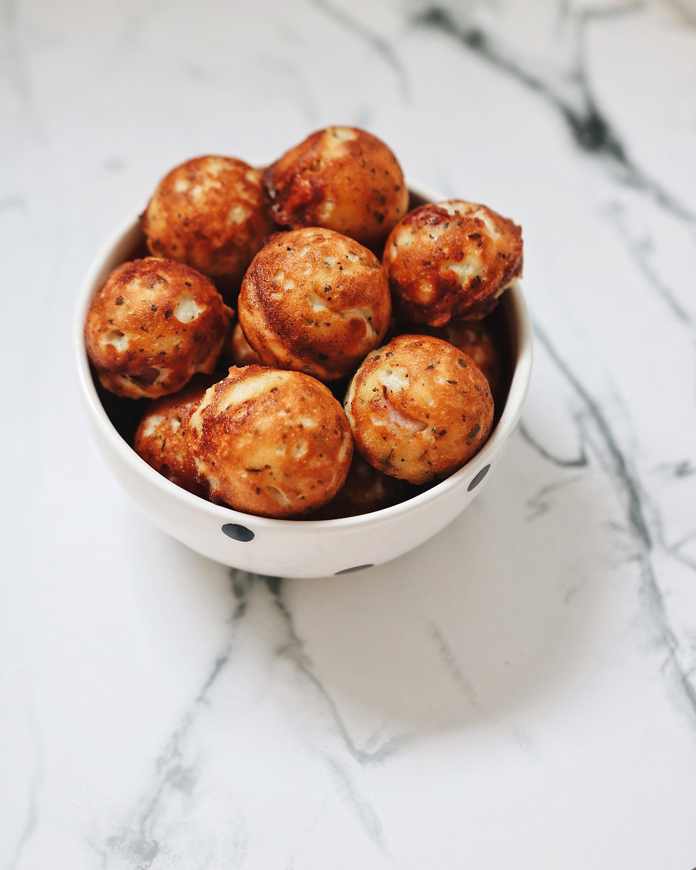 Gluten Free Skyr, Cheddar and Pancetta Bites in a bowl on a white marble background.