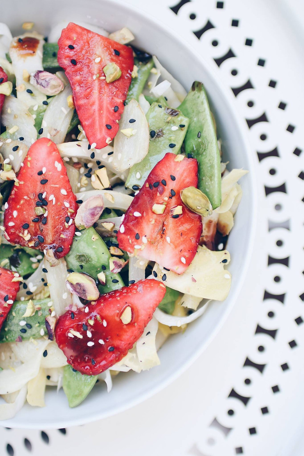 A flatlay view of a plate on a white table. A spring salad of green beans, fennel, strawberries and pistachios with sesame seeds.