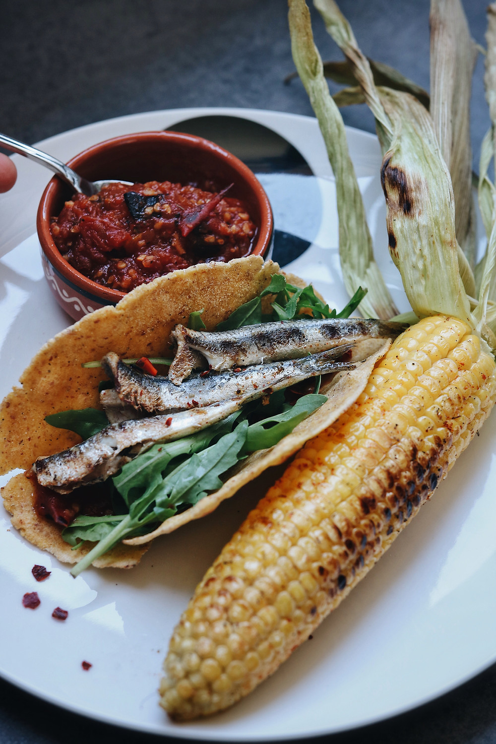 A corn fish taco on a white plate, corn on the cob, and salsa in the background.