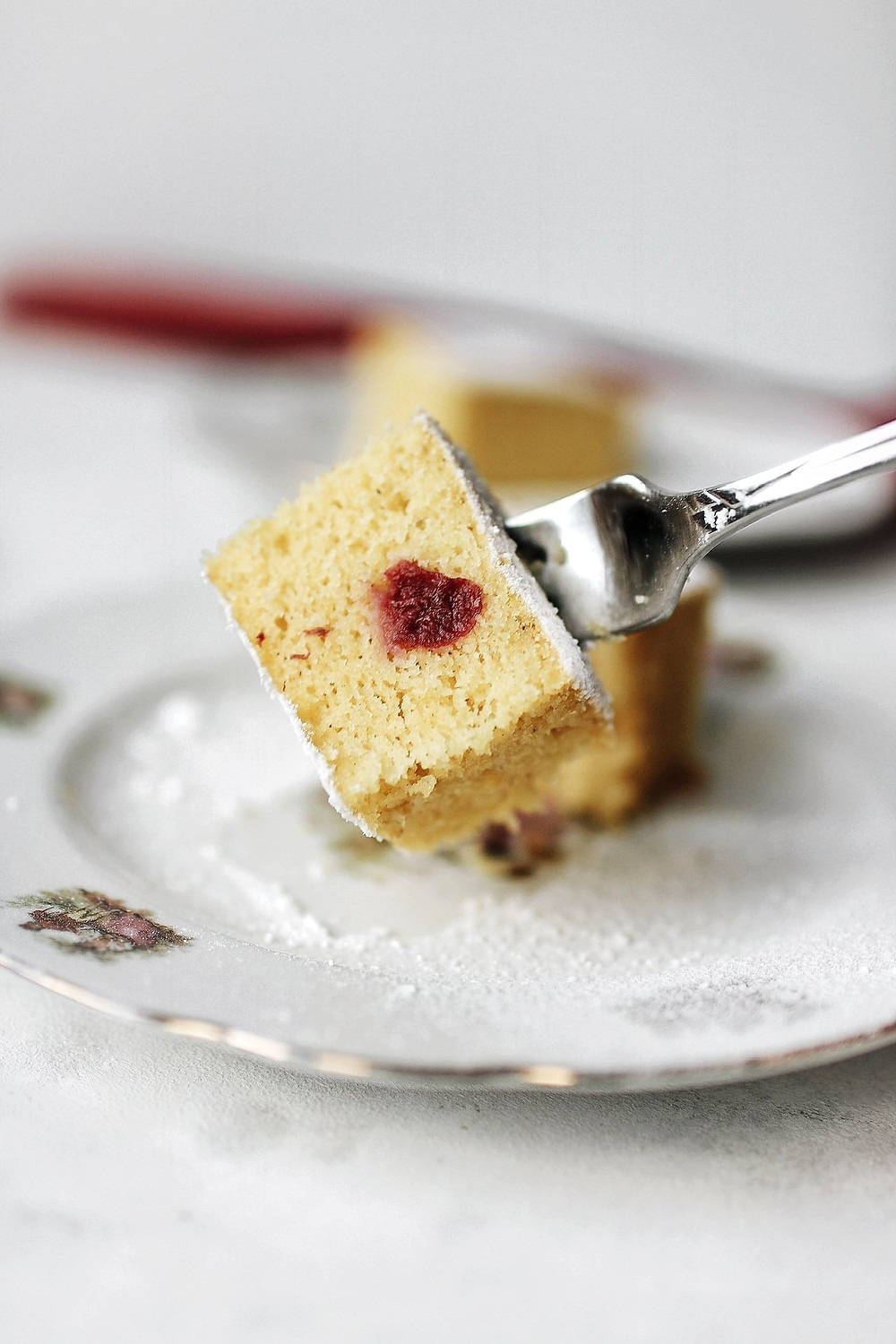 A gluten free and dairy free cornmeal and sour cherry cake piece on a fork.