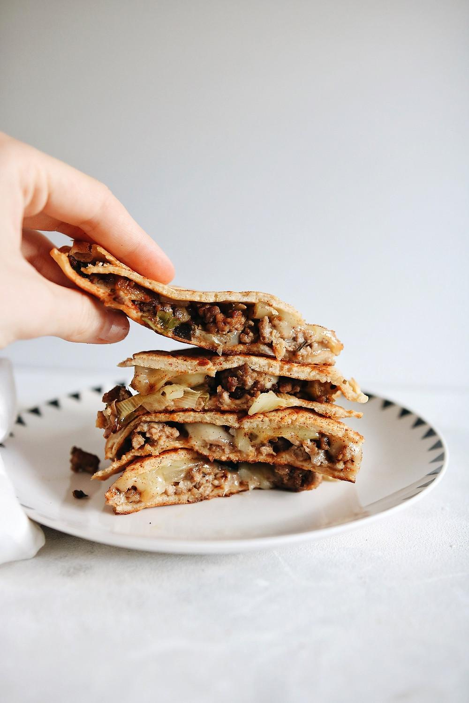 Bezglutenske quesadille od zobenih palačinki s mesom, poslagane na tanjuru, ruka uzima jedan komad.