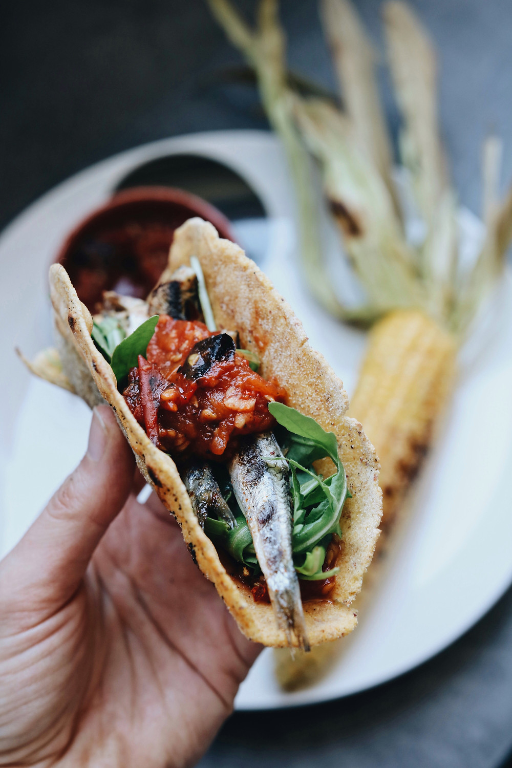 A hand holds a fish taco with arugula, anchovies and salsa.