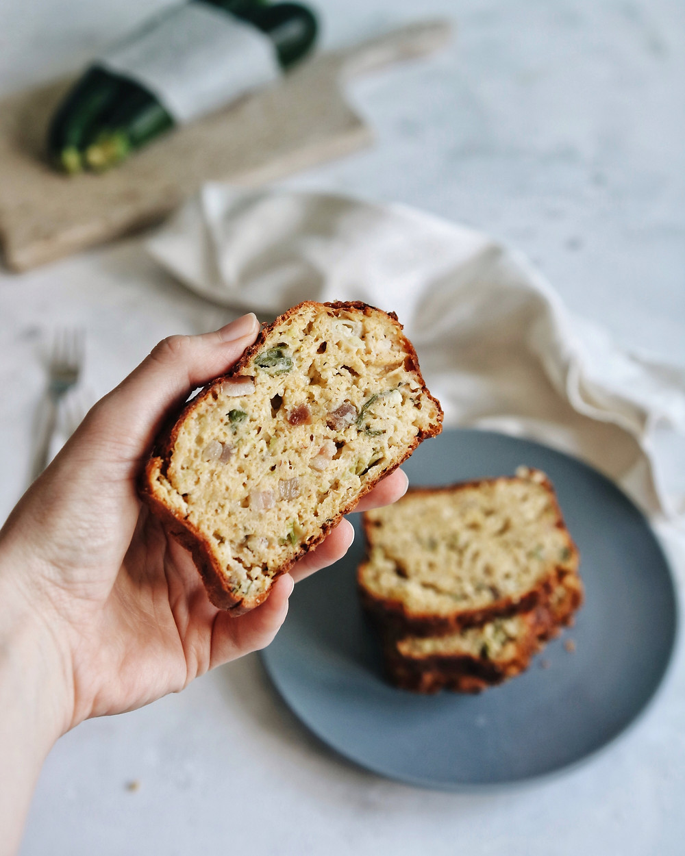 A hand holds a slice of savory zucchini bread with pancetta, cheddar and spring onion.
