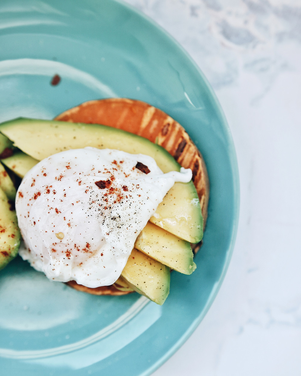 A blue plate with sweet potato toast, on top of which are avocado slices and a poached egg sprinkled with pepper and chili flakes