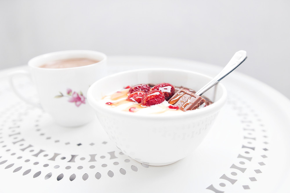 A floral cup of coffee sits on table. Next to it, a bowl with a chocolate avocado pudding, yogurt, raspberries and honey.