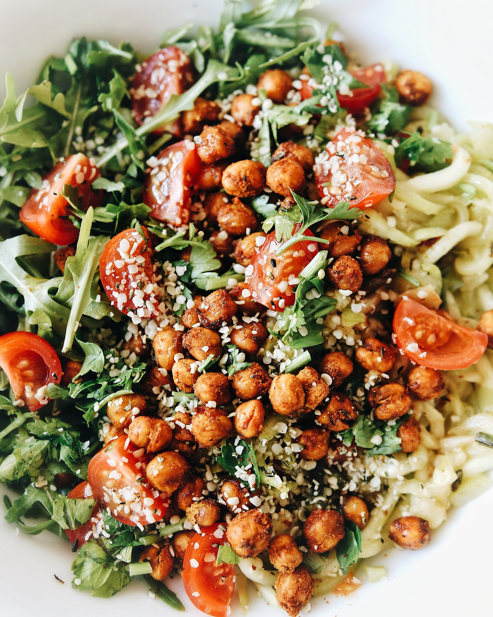 A gluten free zucchini noodle salad with arugula and chickpeas, birdseye view.