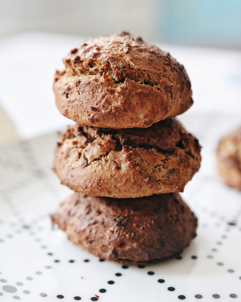 A trio of gluten free banana bread cookies sit on top of each other, forming a tower.