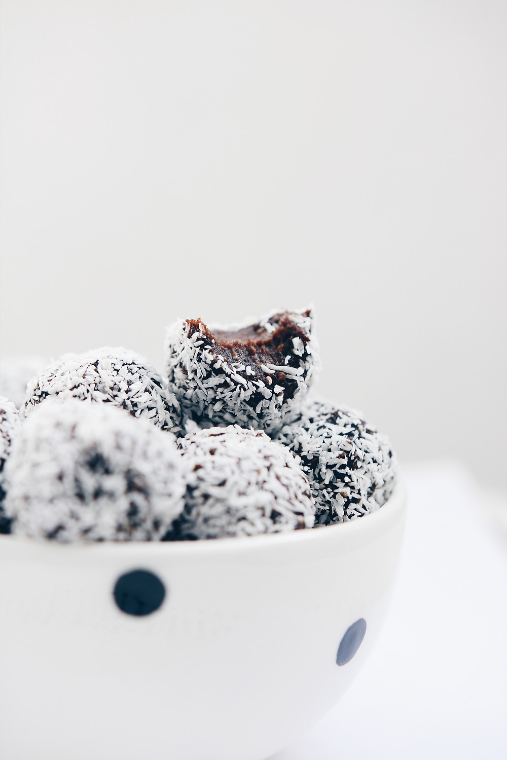 A polka dot ceramic bowl full of energy bite balls. The energy ball on top of the pile has a bite taken out of it.