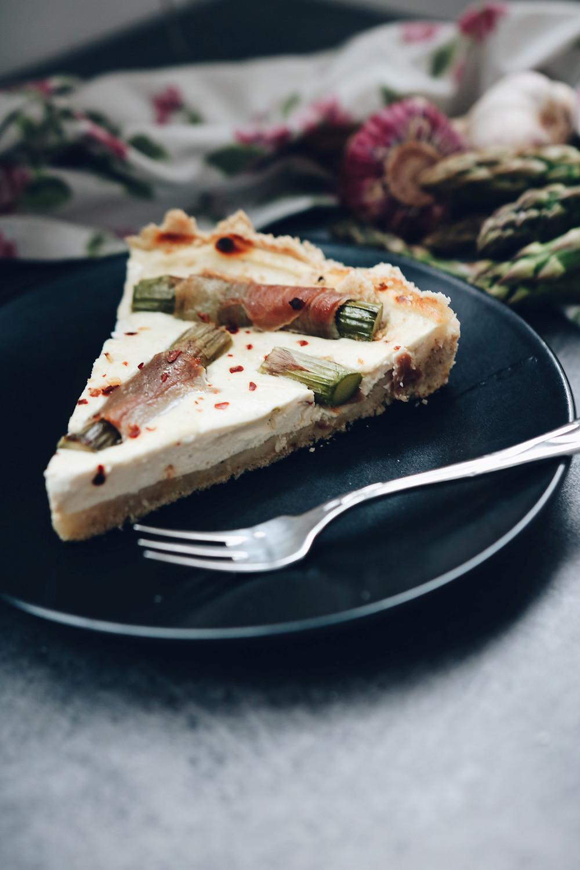 Izrezani komad tarta od kozjeg sira sa šparogama i pršutom, na crnom tanjuriću.