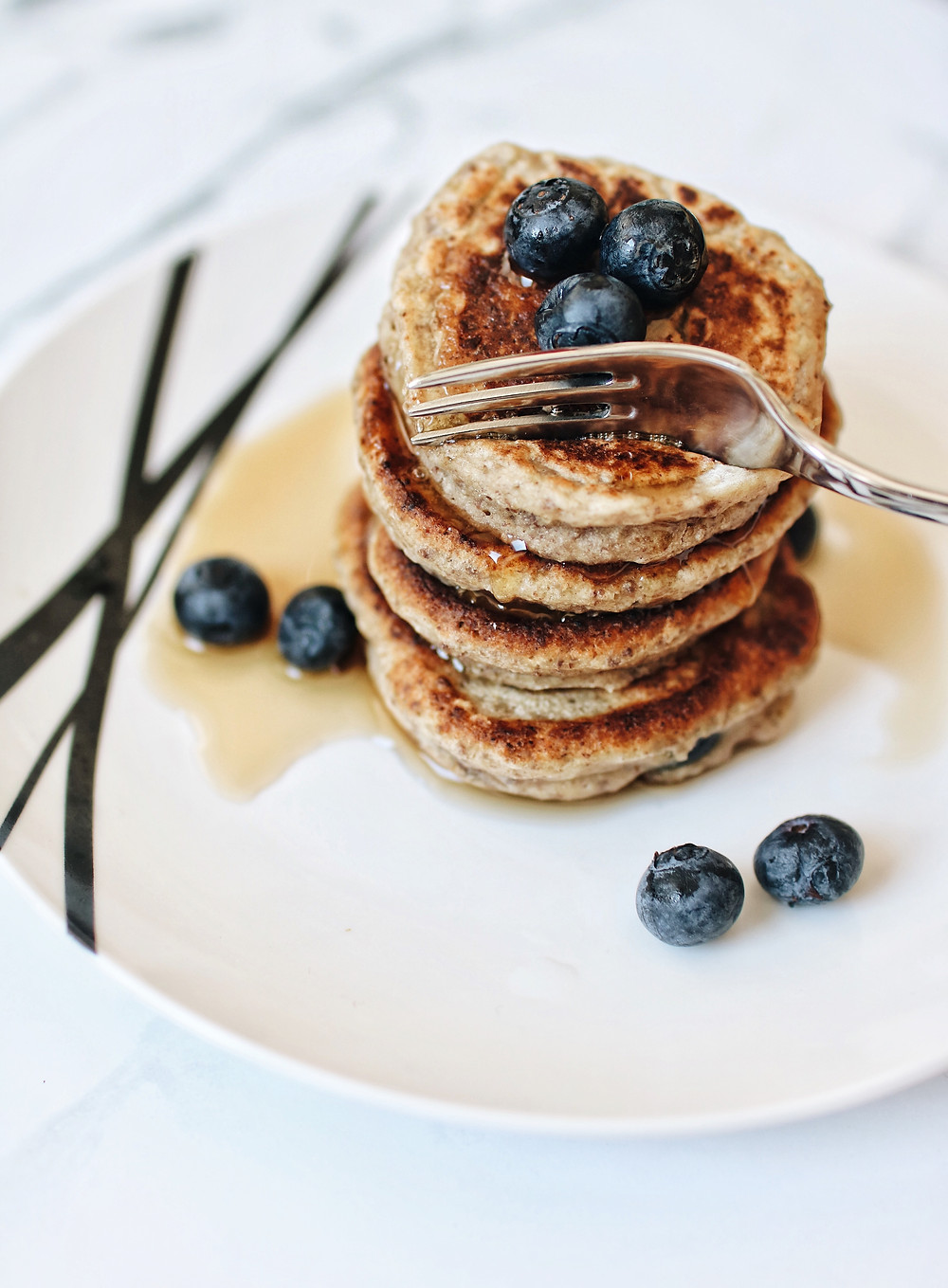 Gluten free blueberry oatmeal pancakes stacked on a plate, with fresh blueberries and maple syrup.