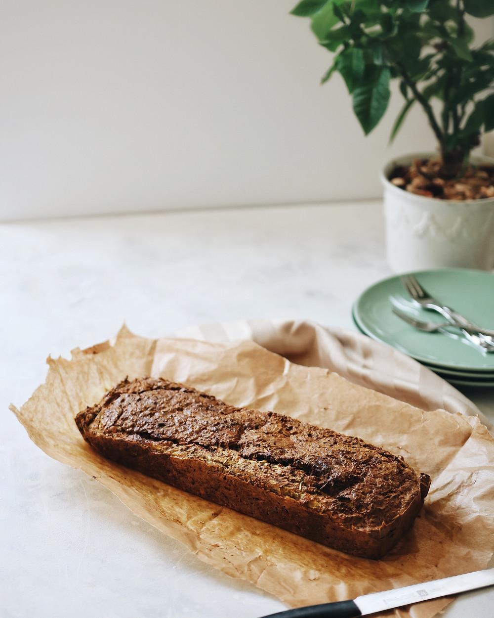 Zlatni kruh od tikvica na bijeloj podlozi, na papiru za pečenje. U pozadini tanjuri i biljka.