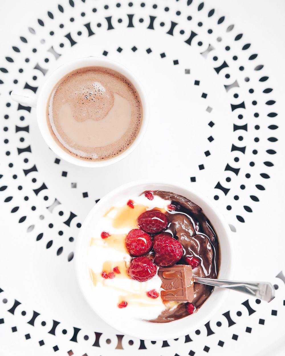 Birds eye view of a white table. Coffee with milk is in the upper left corner. In the lower right corner there is a breakfast bowl wit chocolate avocado pudding and yogurt, raspberries, chocolate and honey.
