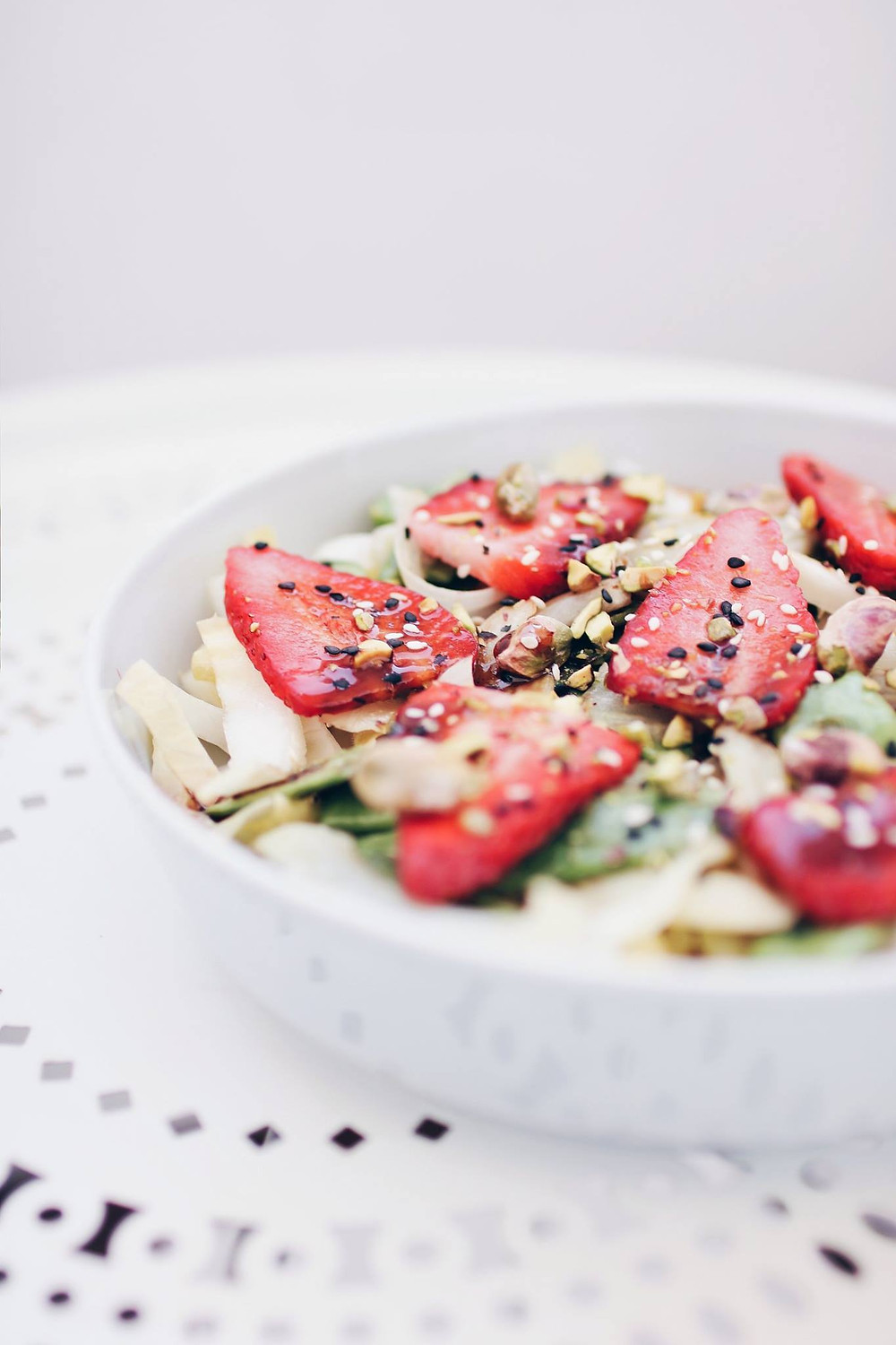 A serving dish sits on a white table. A warm and cold salad sits in the dish, consisting of green beans, fennel and endive, along with strawberries, sesame seeds, pistachios and a balsamic reduction.