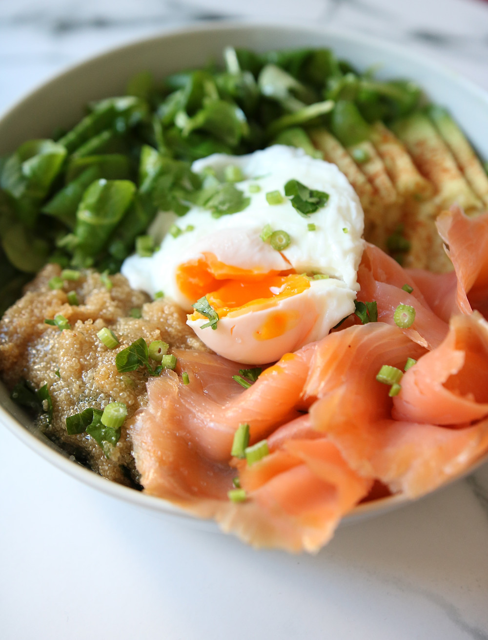 A cracked poached egg sits on top of smoked salmon, amaranth, salad greens and avocado.