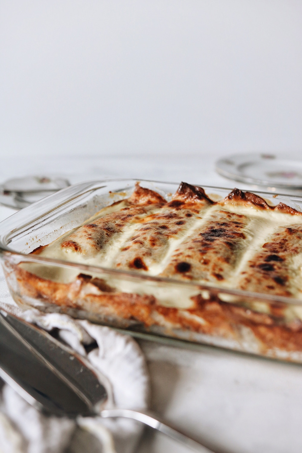 A baking pan filled with gluten free baked savory crepes filled with fresh cheese, cooked swiss chard and pancetta.