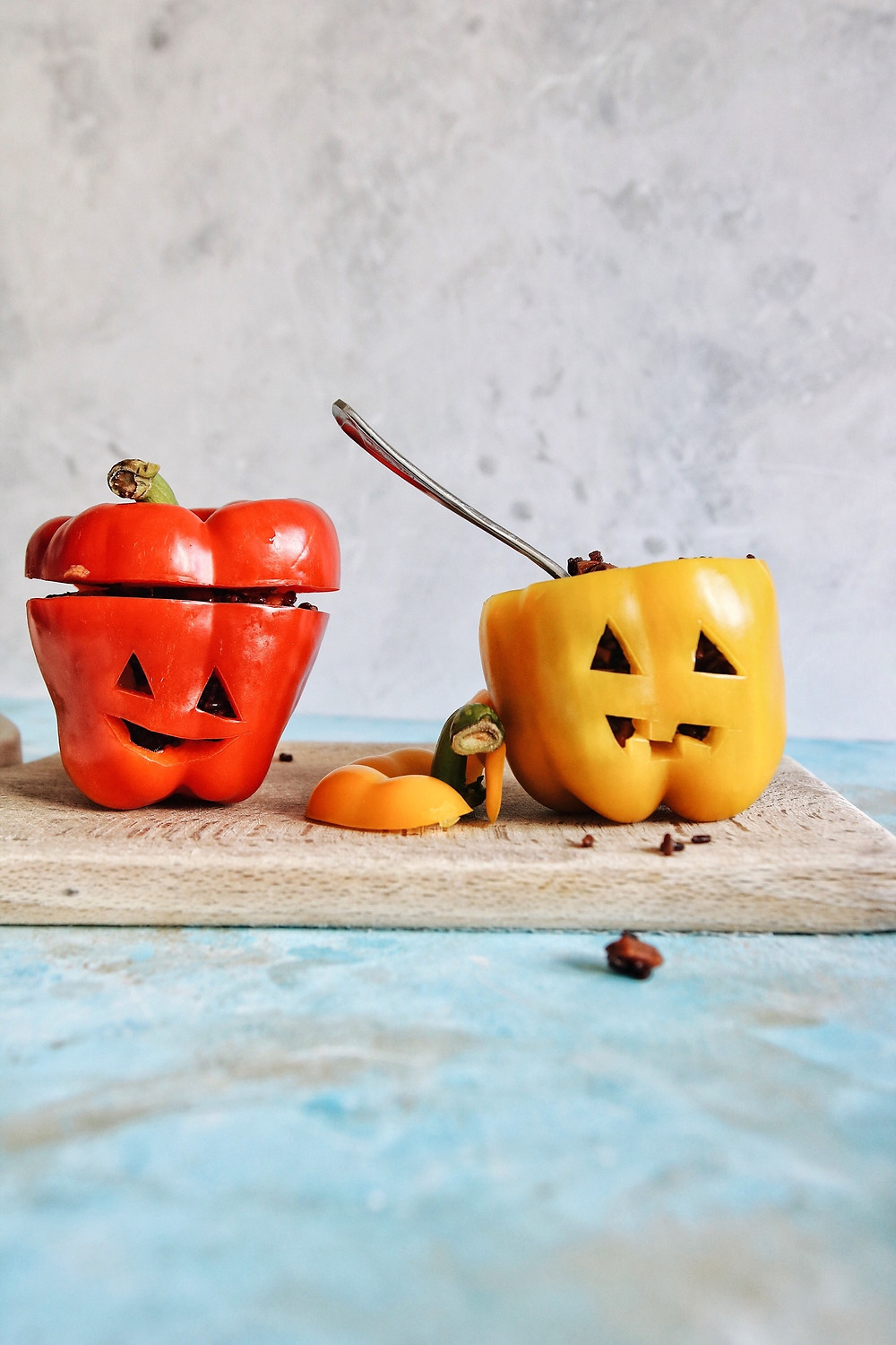 A red and yellow bell pepper sit side by side, both carved like jack o lanterns and stuffed with a gluten free rice risotto.