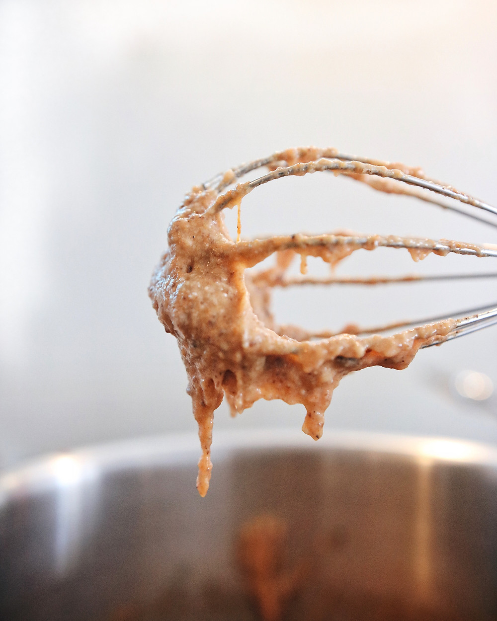 A whisk is in the air, while porridge drips from it.