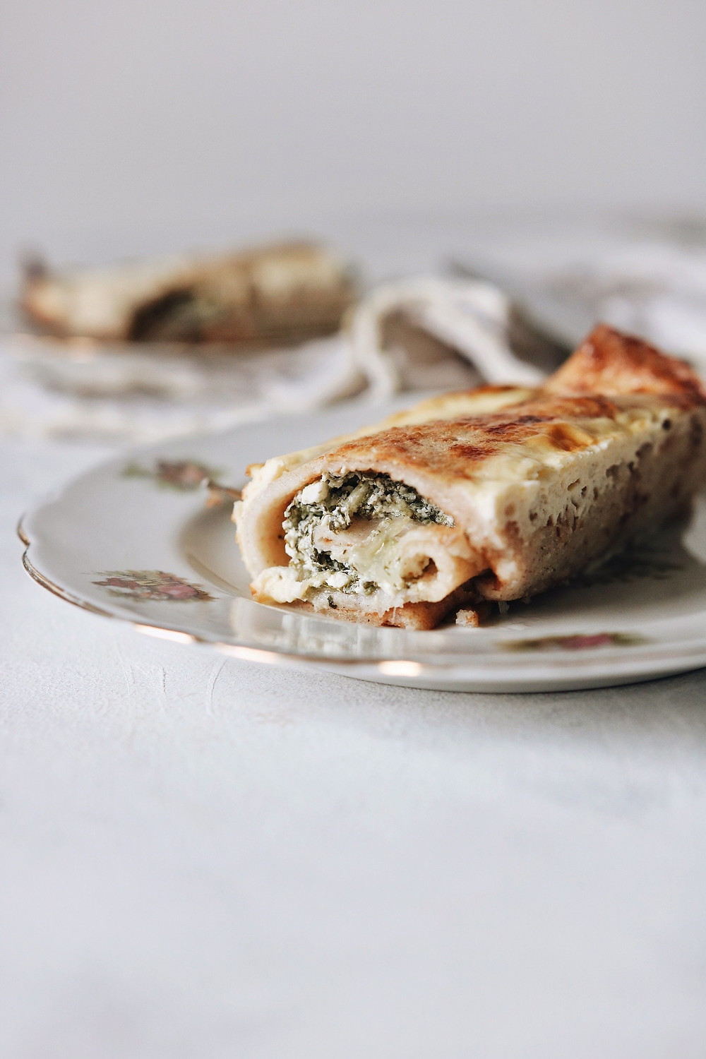 A single baked savory crepe on a plate, filled with swiss chard, cheese, and bacon (pancetta).