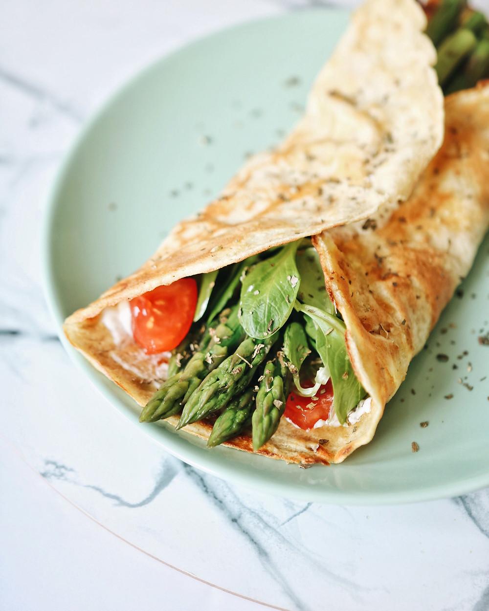 Slane palačinke bez glutena, sa šparogama, rajčicama i matovilcem na zelenom tanjuru.