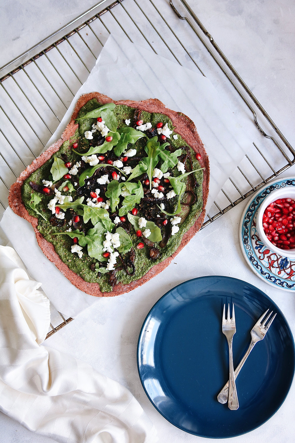 A beetroot crust pizza on a white backround, a cooling rack, blue plate and pomegranate seeds on the side.