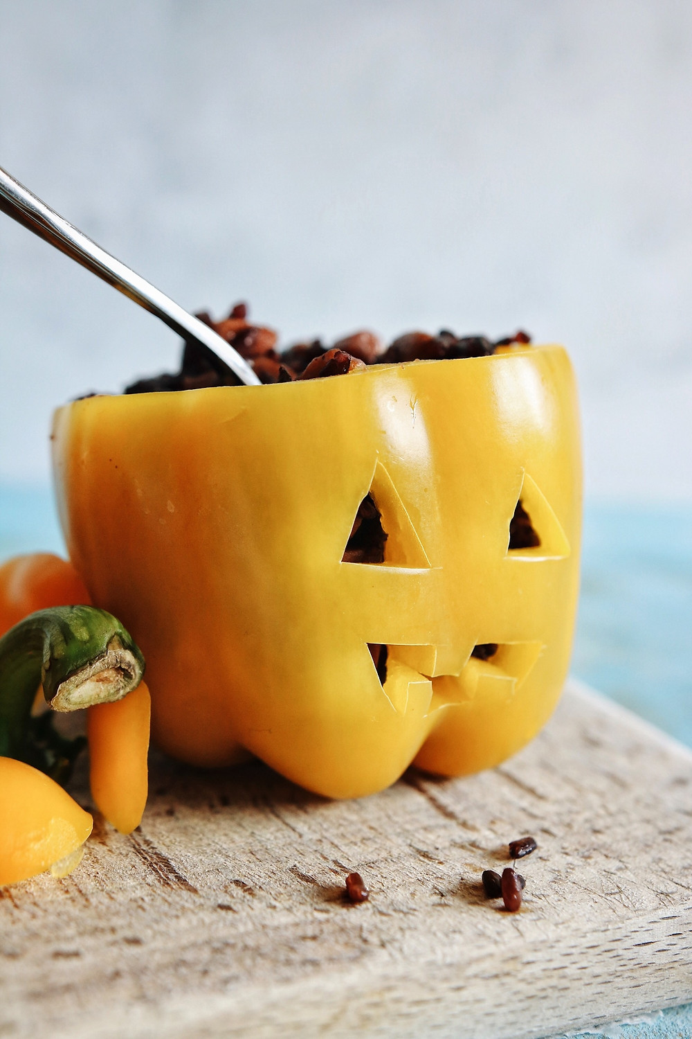 A yellow bell pepper carved like a jack o lantern and stuffed with a black risotto.