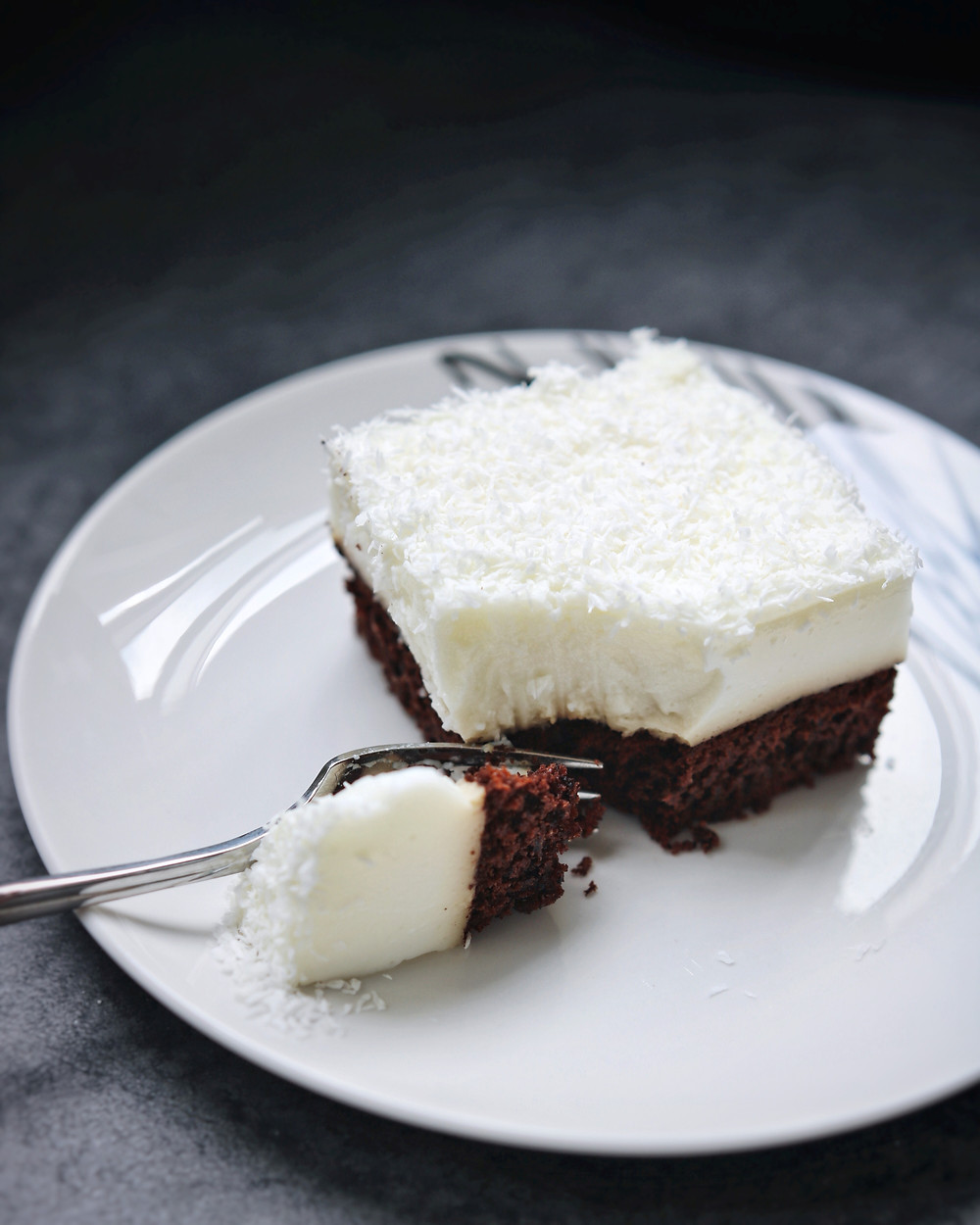 A fork takes out a bite of the gluten free coconut and chocolate cake bar.