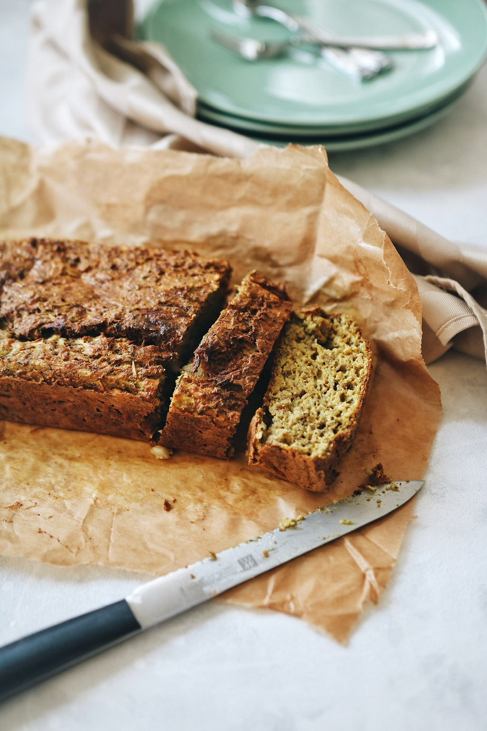 A gluten free golden zucchini bread sliced and filled with warming spices, a knife in the foreground and plates in the background.