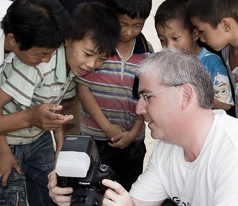 שרון ינאי מוקף בילדים מסתכלים על צילום