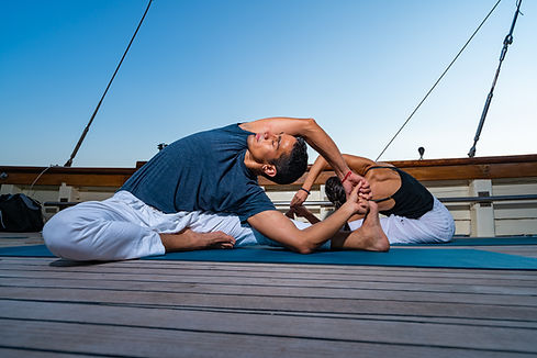 Couple practicing Yoga on a sailing yach