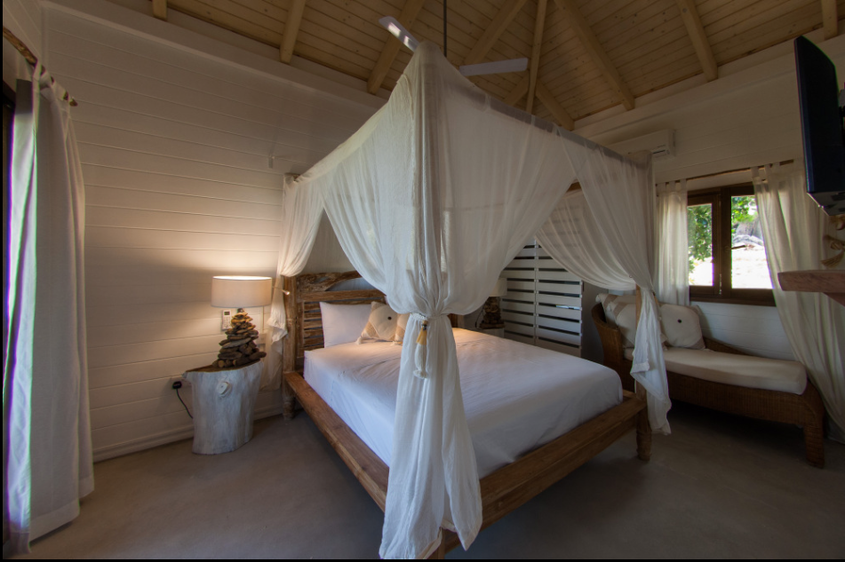 Luxurious bedroom with views out to the trees and sea