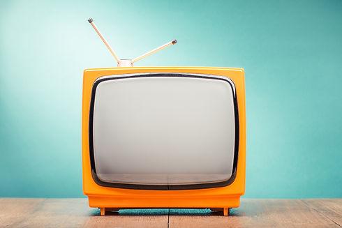 Retro old orange TV set receiver on wood