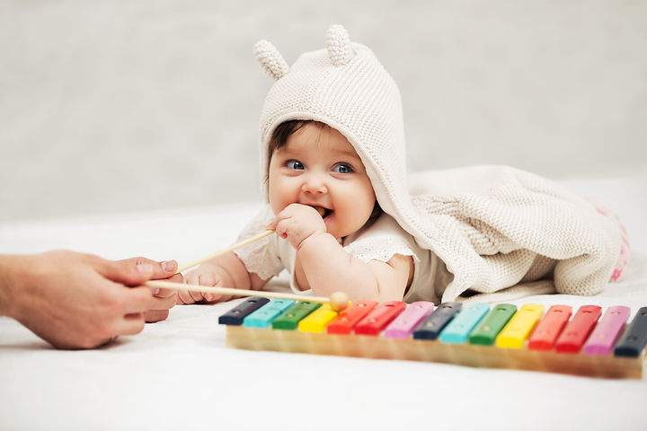 Baby girl playing with xylophone toy on