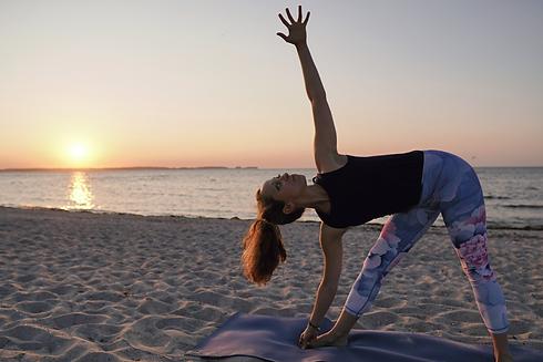 Trikonasana (Dreiecksposition) mit Ashtanga Yogalehrerin Michaela Styppa am Strand von Kiel