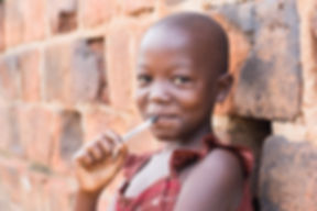 Ugandan Girl placing pen on lips while leaning on a stone wall.