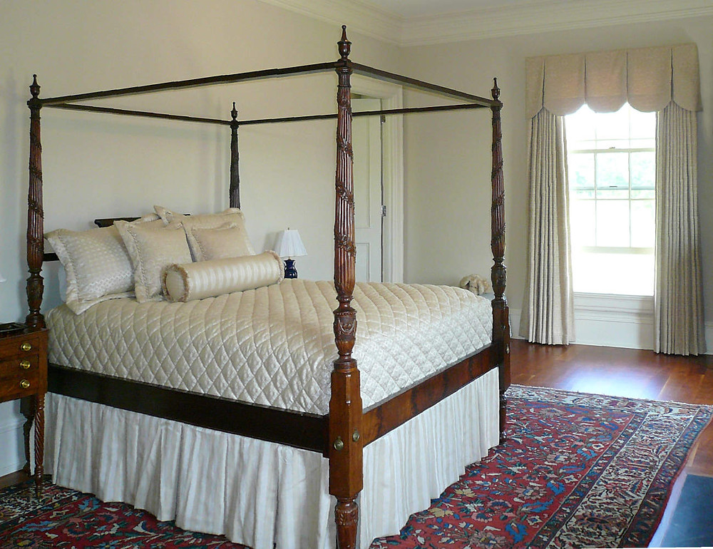 Canopy bed with custom pillows and window treatment.