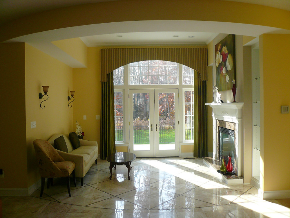 Yellow room with tall window treatments and cozy fireplace.