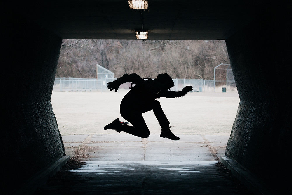 Break dancer in silhouette in a pose mid-air in a tunnel.