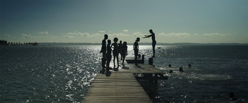 A color image of the silhouettes of 7 people standing in a wooden dock over a lake with sparkling water, in a bright sunny day. One of them is jumping backwards into the water where there are two people swimming. In the background the blue sky with some white clouds and an outline of a mountain. Overlaid in white capital letters the words: A Spiritual Journey.