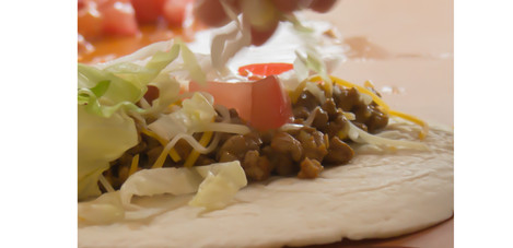 Putting lettuce on taco (Spanish Chef Project)