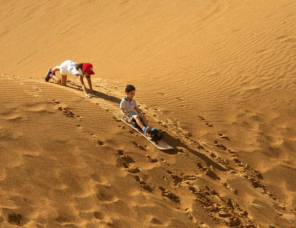 Boy and girl, sand dunes, sand boarding, Dubai